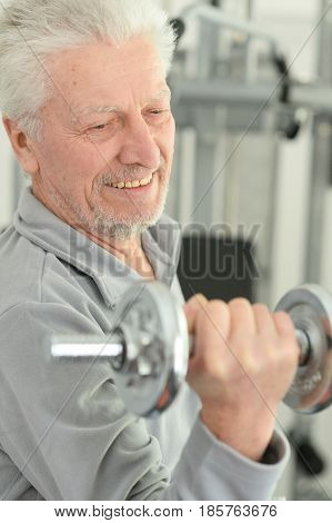 Portrait of an elderly  man in a gym with dumbbells