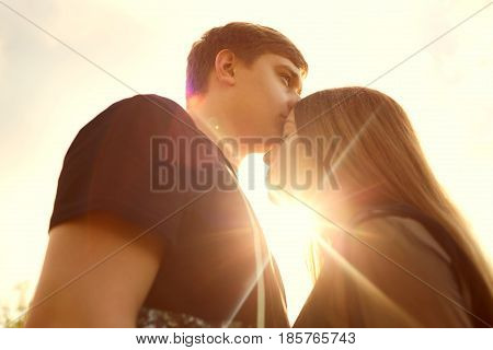 The concept of love and relationships. Guy and a girl are kissing in the sun at sunset.