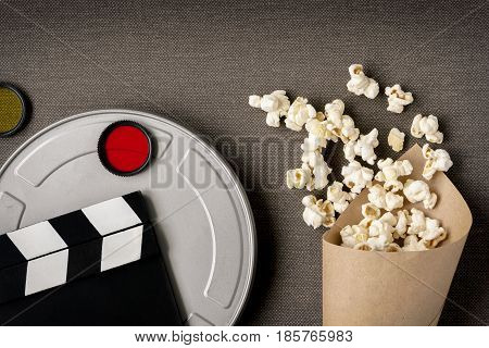 Clapperboardbox with movie package with popcorn and color filters photographed above