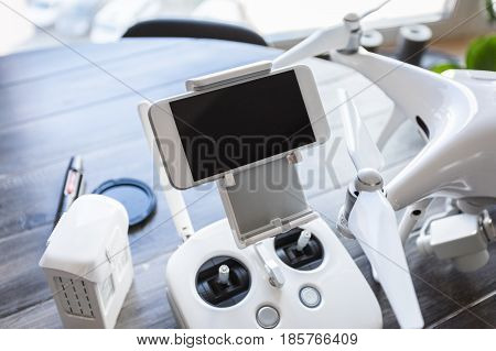 Drone with a control panel on the background of a dark wooden table. Aerial shooting concept. Before flight training. Top view. Outfit before the flight.