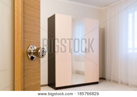 Ajar door to the room with a cupboard poster
