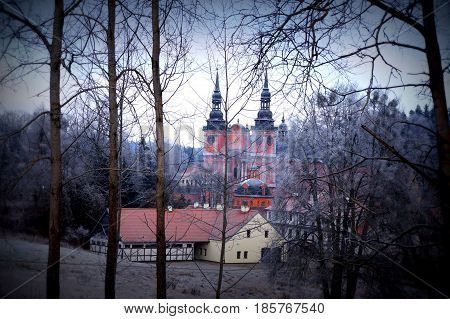 View of an old church through a gloomy winter forest