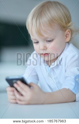 Little boy is playing with a mobile phone