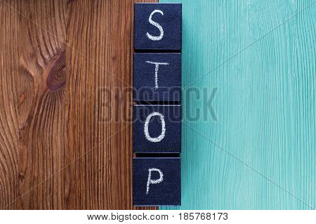 Concept of word Stop contradistinction or versus. Word STOP on wooden cubes separates and contrasts the wooden background. Two-colored wooden background antonym concept.
