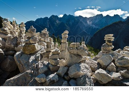 Pile of rocks in front of mountain peaks of slovenian Alps at sunny morning near Vrsic mountain pass in Triglav national park, Slovenia