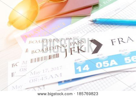 Airline boarding pass tickets with travel insurance, passports, sunglasses, pen as a concept of traveling