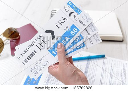 Airline boarding pass tickets in haand with travel insurance, passports, sunglasses, pen and notebook as a concept of traveling