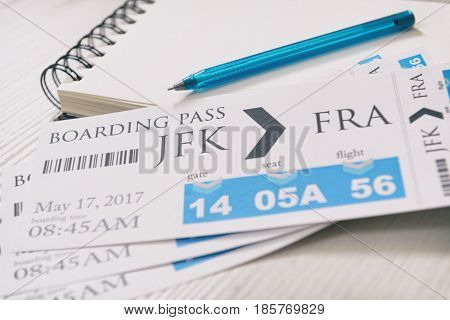 Airline boarding pass tickets with notebook and pen