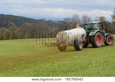 Farmers fertilize meadow with manure - close-up with manure fertilizer
