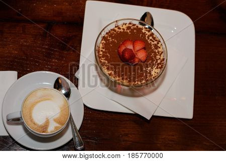Delicious coffee with milk froth and sweet dessert