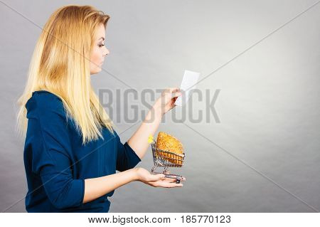 Happy woman holding shopping basket with bread looking at receipt bill thinking about prices.