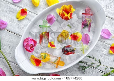 Homemade popsicles with flowers in serving dish on wooden table