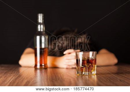 Drunk Woman Sleeping At Bar Counter with a Bottle and a Glass of Whisky
