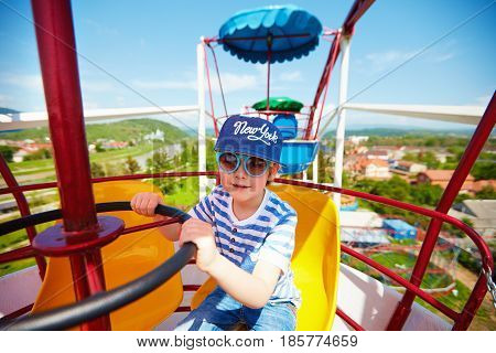Excited Kid Riding On Ferris Wheel In Amusement Park