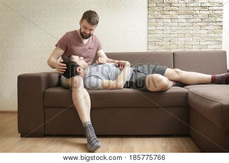 Happy gay couple resting on sofa at home