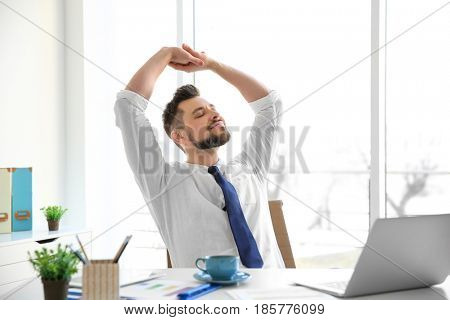 Happy young man sitting at table in office and stretching himself