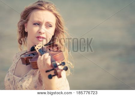 Music love hobby and everyday passion concept. Woman on beach near sea playing on violin