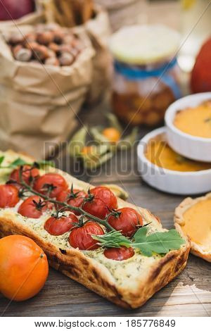 Pie with cherry tomatoes, pumpkin pie, orange and paper bag with nuts on a wooden table