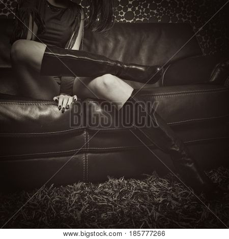 fashion girl in high heel leather  boots sit on leather sofa indoor shot sepia tones lower body