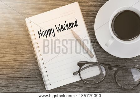 Concept Happy Weekend message on notebook with glasses pencil and coffee cup on wooden table.