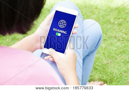 Top view of woman using her mobile phone with checking roaming on her mobile phone.