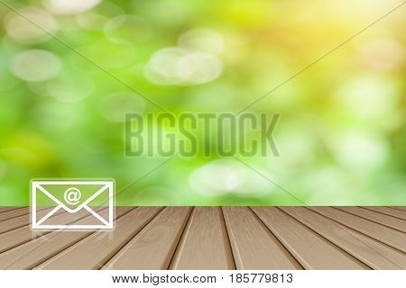 Contact us Button concept Wooden board empty top table with mail and @ blurred tree with bokeh background - can be used for display or montage your products and text.