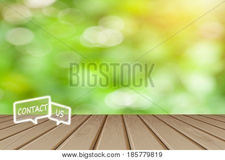 Contact us Button concept Wooden board empty top table icon with blurred tree with bokeh background - can be used for display or montage your products and text.