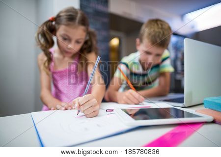 Siblings doing their homework in kitchen at home