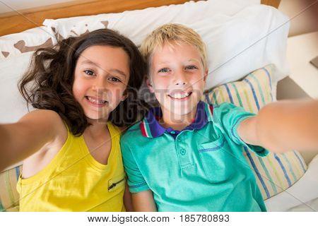 Smiling siblings taking selfie in bedroom at home