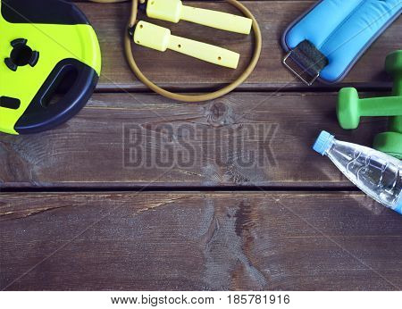 Female sport equipment and pure water on a wooden background. Sports items on the wooden background. Set for sports activities in the gym