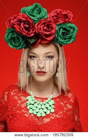 portrait woman in red dress with red and green flower wreath