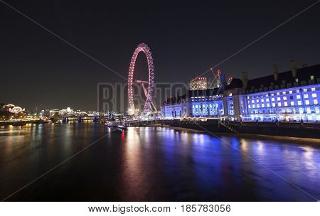London, UK - 24 January 2017:  Illumination of the London Eye and the buildings next to River Thames.