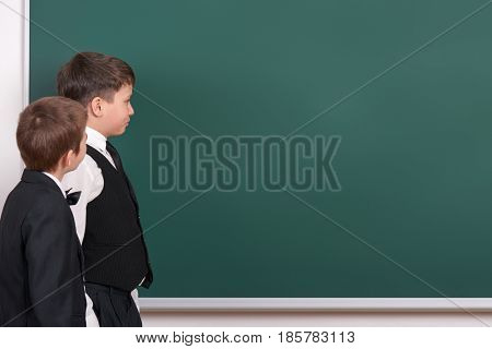 elementary school boy look on blank chalkboard background, dressed in classic black suit, group pupil, education concept