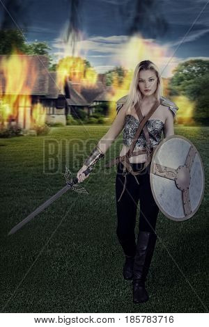 woman warrior walking away from burning village