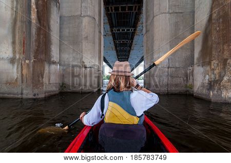 Woman paddling a kayak in the river between bridge supports. Kayaking in the city. Urban summer adventure concept.