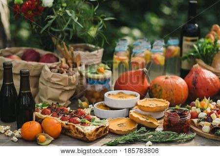 Picnic in nature with a pie with cherry tomatoes, pumpkin pies, wine, sun-dried tomatoes, lemonade, cheese, pumpkin and other snacks on a wooden table
