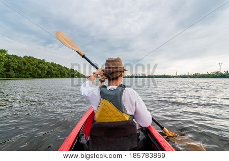 Unrecognizable Young girl kayaking on a river or lake. Happy girl canoeing on a summer day
