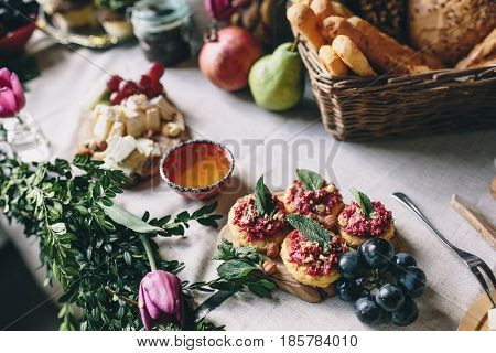Snack from crackers and beets, grapes, honey, cheese. Wicker basket with bread on the table decorated with flowers and boxwood