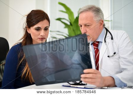 Doctor showing a knee radiography to a patient