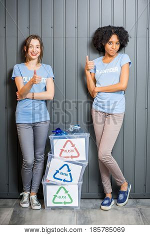 Young female volunteers in blue t-shirts standing with containers with sorted waste indoors