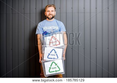 Male volunteer in blue t-shirt holding containers with sorted waste standing indoors on the gray wall background