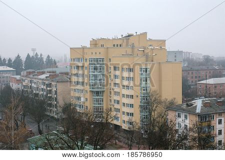 New residential building among constructions of Soviet Union times at fog