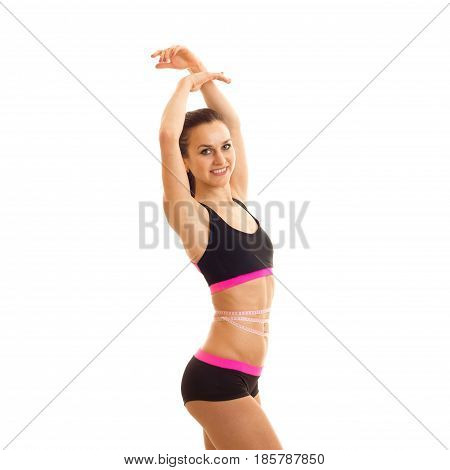 charming young girl in sports top and short shorts posing on camera holding up hands up and smiling isolated on a white background