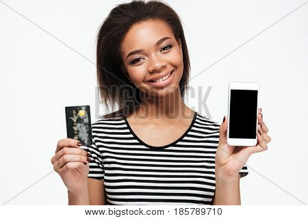 Image of happy young african lady standing isolated over white background. Looking at camera while using phone and holding debit card.