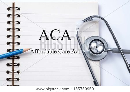 Notebook and pencil with ACA Affordable Care Act on the table with stethoscope medical concept