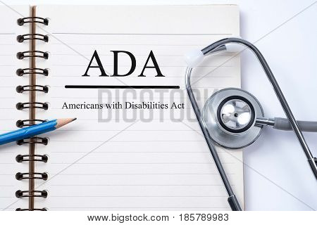 Stethoscope on notebook and pencil with ADA (Americans with Disabilities Act) words as medical concept.