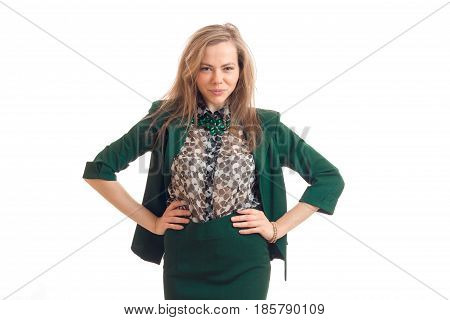 sexy young blonde in a green suit looks cunning gaze and keeps her hands on the sides of the isolated on white background