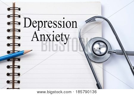 Stethoscope on notebook and pencil with Depression Anxiety words as medical concept.