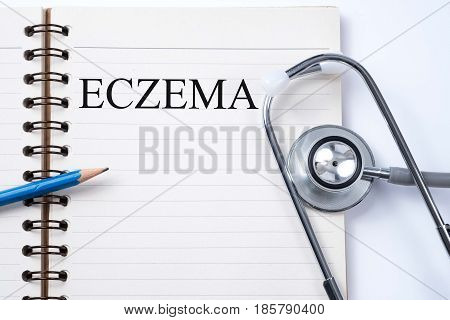 Notebook and pencil with Eczema on the table with stethoscope medical concept