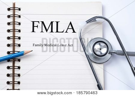 Stethoscope on notebook and pencil with FMLA family medical leave act words as medical concept